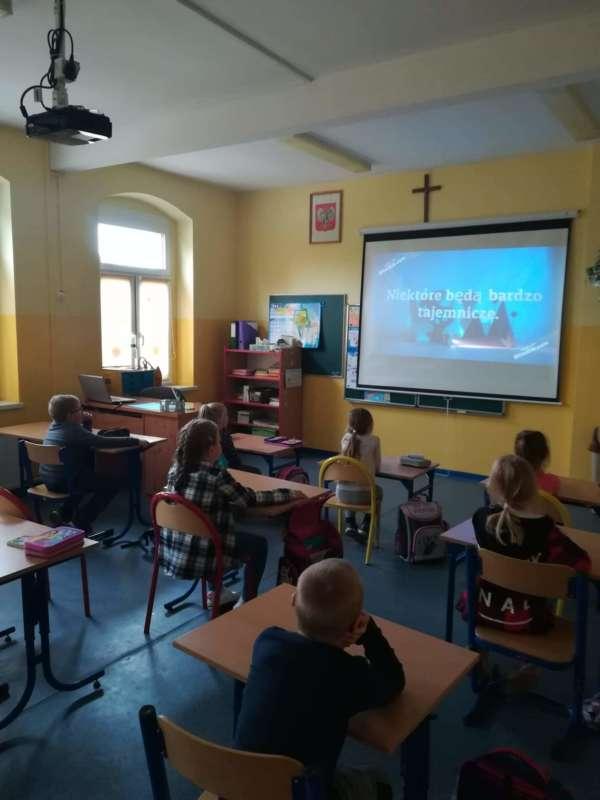 Dzieci siedzące w ławkach w klasie oglądają film na zawieszonym na ścianie monitorze.