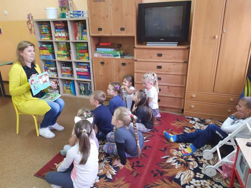 Pani Kasia z biblioteki wiejskiej pokazuje obrazki z książki zgromadzonej przed nią na dywanie grupce dzieci.