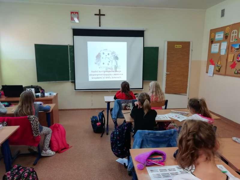 Dzieci siedzące w ławkach w klasie oglądają film, na zawieszonym na ścianie ekranie.