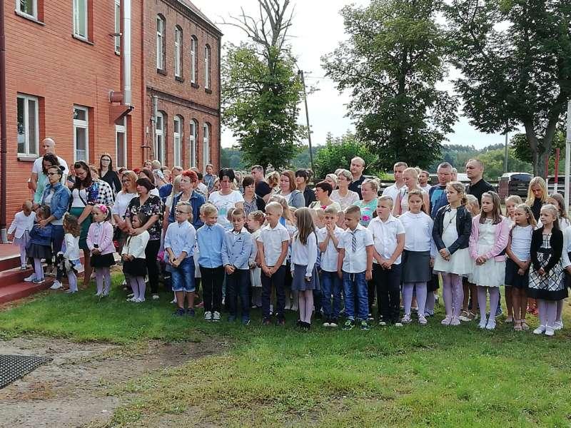 Dzieci ubrane na galowo stoją w dwuszeregu wraz z rodzicami przed budynkiem szkoły.