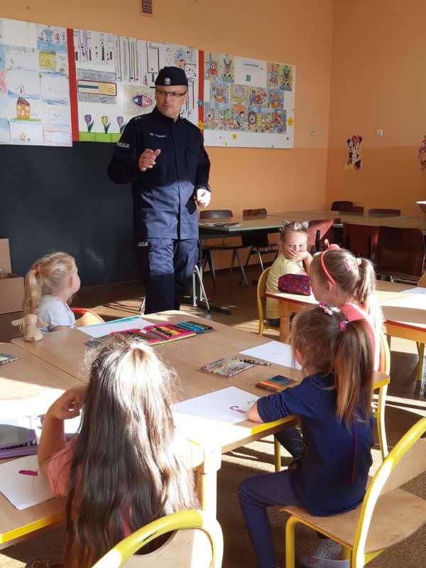 Mężczyzna w stroju policjanta stoi na środku klasy przed siedzącymi w ławkach dziećmi.