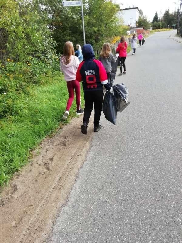 Dzieci niosące worki foliowe sprzątają pobocze drogi przy lesie.