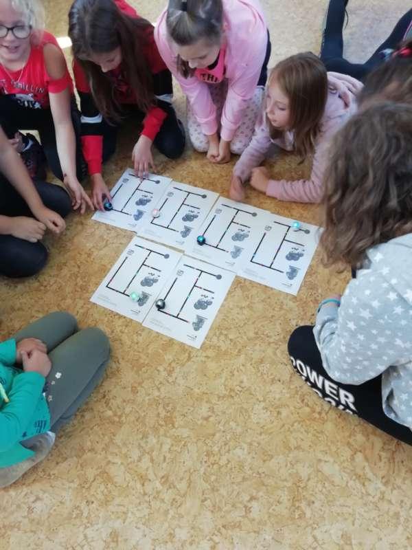Siedzące na podłodze dzieci tworzą własne trasy dla ozobota.