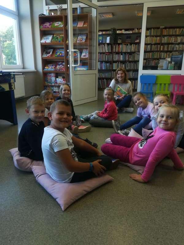 Dzieci wraz z Panią Kasią siedzą na poduszkach na podłodze w bibliotece wiejskiej.