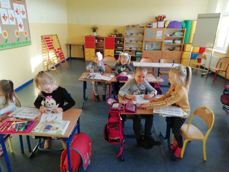 Roześmiane dziewczynki siedzą parami w ławkach szkolnych, kolorując białe karki pisakami.