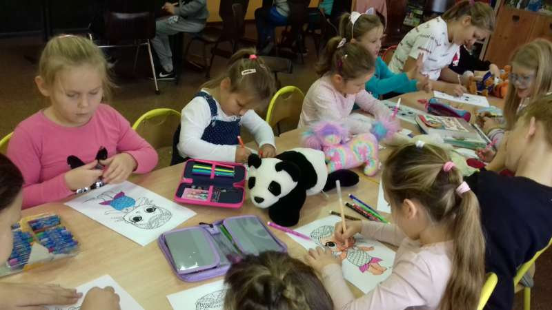 Dzieci siedzą przy połączonych stołach kolorując obrazki postaci z bajek.