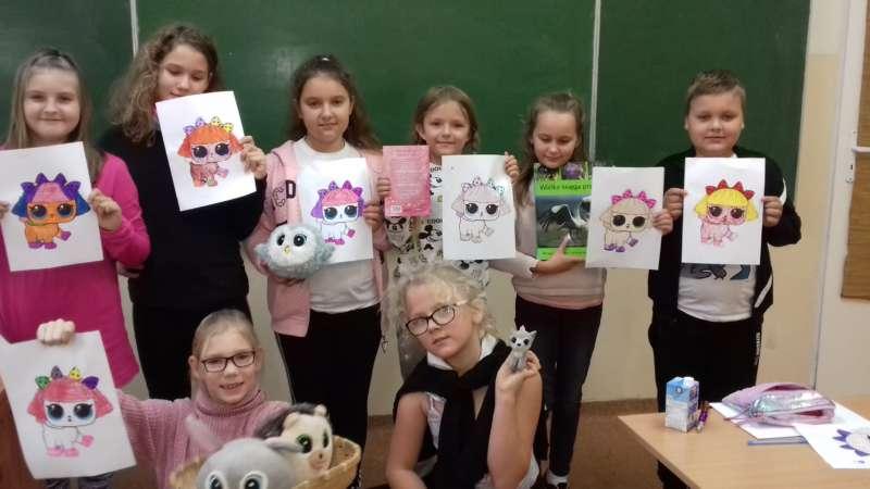Dzieci stojące przy tablicy na środku klasy, prezentują wykonane przez siebie kolorowanki.