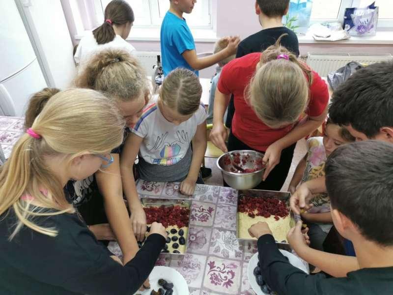 Zgdromadzone przy stole kochennym dzieci nakładają z garnków owocoe na ciasto drożdżowe w brytfannie.