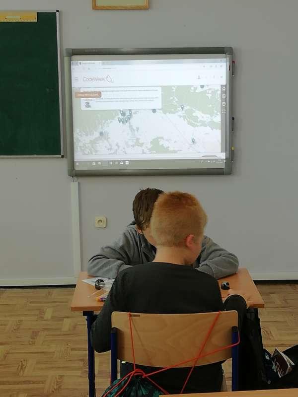 Dwóch chłopców siedzi na przeciw siebie przy ławce szkolnej. W tle zawieszony na ścianie włączony monitor.