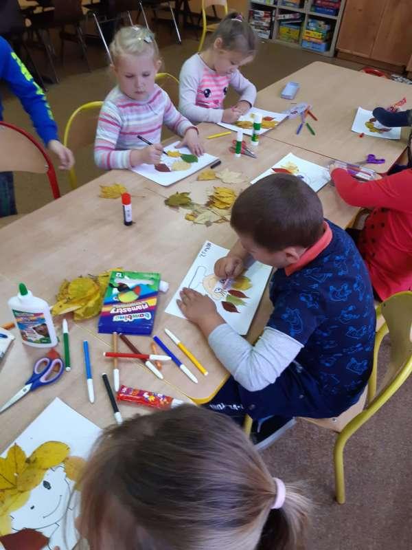 Dzieci siedzące przy połączonych ławkach wykonują prace plastyczne na kartkach z wykorzystaniem pisaków oraz jesiennych liści.