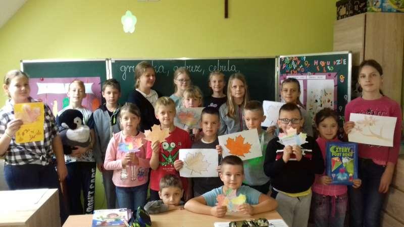 Dzieci stoją przy tablicy na środku klasy, trzymając kartki z wykonanymi przez siebie kolorowankami jesiennych liści.