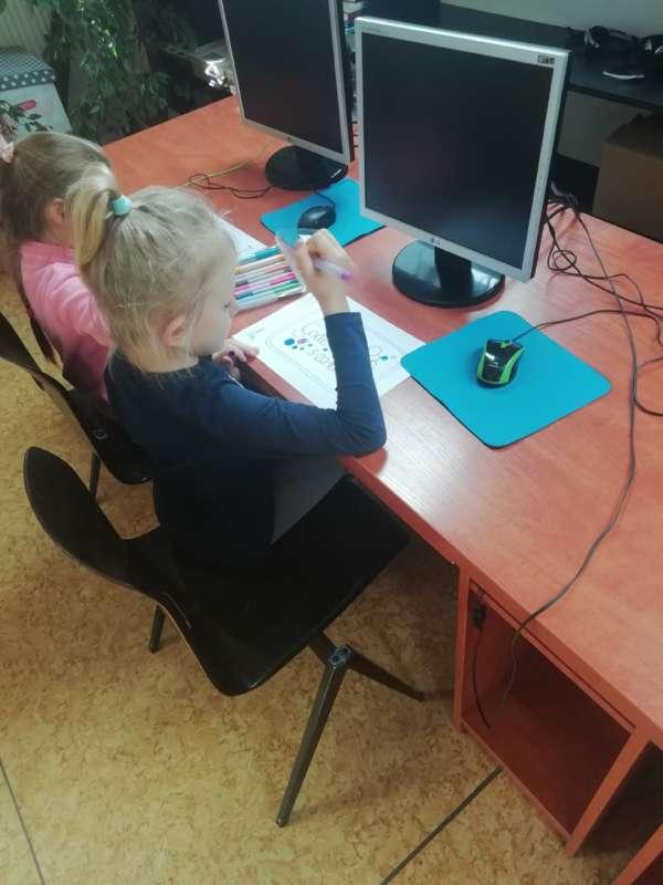 Dwie dziewczynki siedzą przy stołach z monitorami komputerowymi, mając przed sobą kartki papieru, trzymając kolorowe pisaki.
