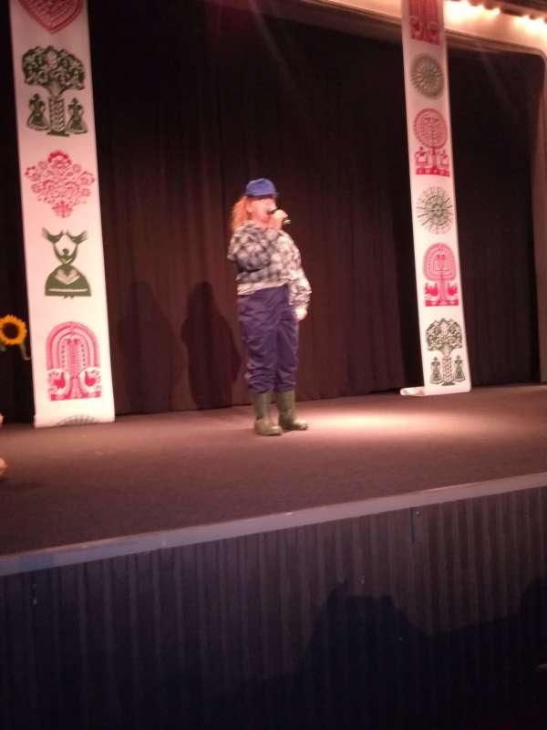 Dziewczynka stoi na środku sceny z mikrofonem w stroju roboczym.