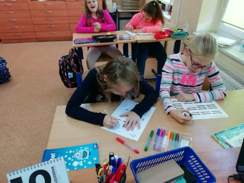 Dziewczynki siedzą parami w ławkach szkolnych, mając przed sobą karki oraz wielokolorowe pisaki.