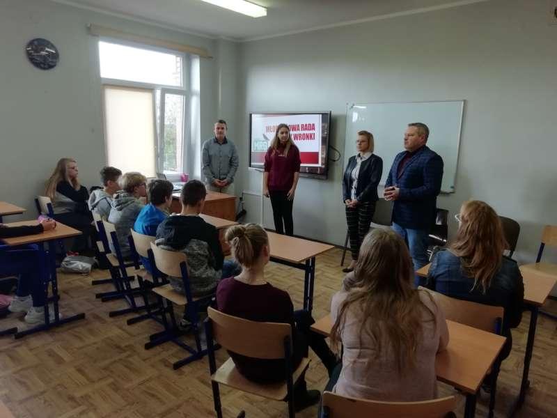 Burmistrz Robert Dorna z pracownikami urzędu stoją na środku klasy przed siedzącymi w ławkach uczniami.