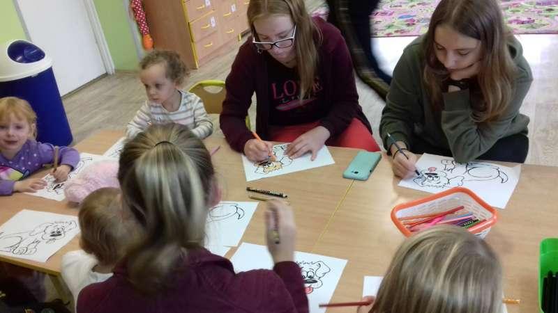 Dzieci siedzące przy połączonych stołach kolorują obrazki z psami.
