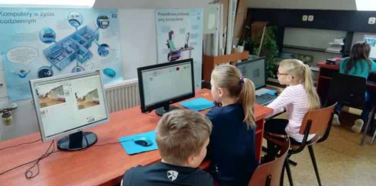 Dzieci siedzą na krzesłach przy monitorach komputerowych.
