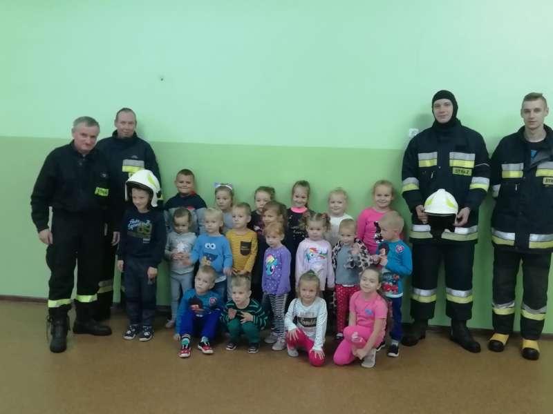 Dzieci pozują do zdjęcia wraz z strażakami przy ścianie sali gimnastycznej.