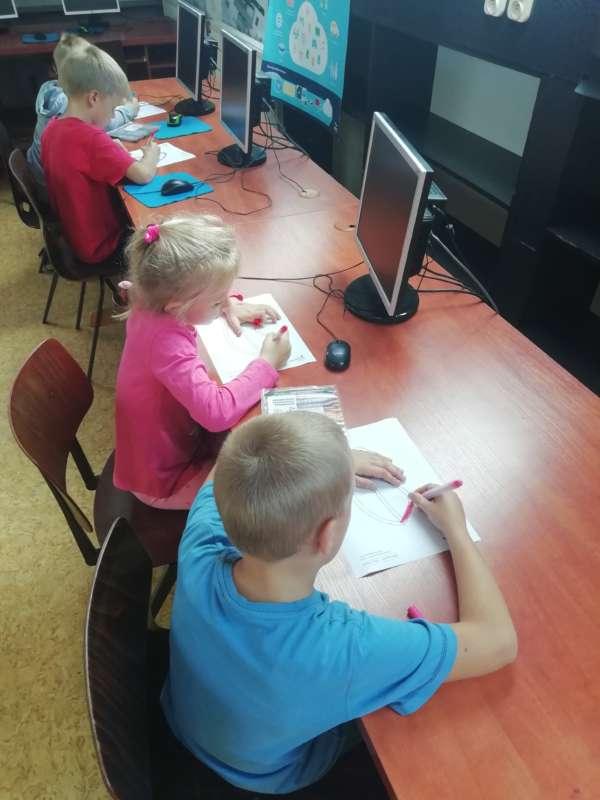 Dzieci siedzą przy stołach z monitorami komputerowymi, kolorując obrazki na ułożonych przed nimi kartkach.