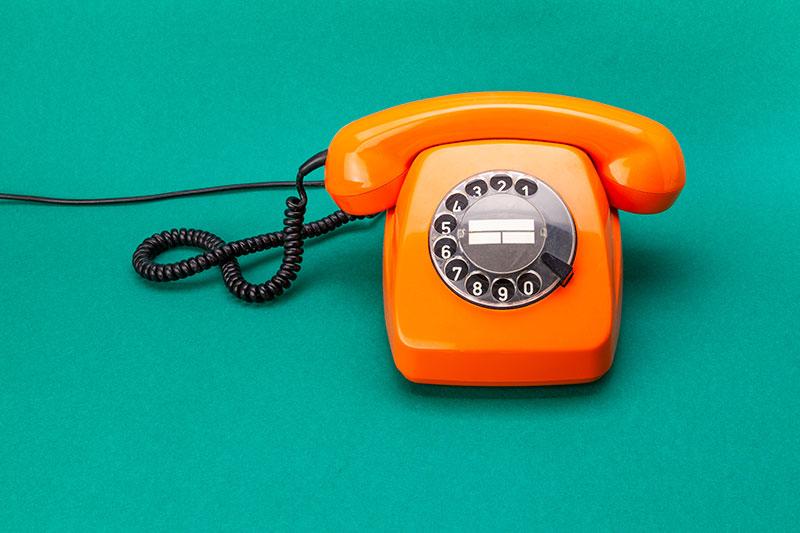 Pomarańczowy telefon z tarczą numerową na zielonym tle.