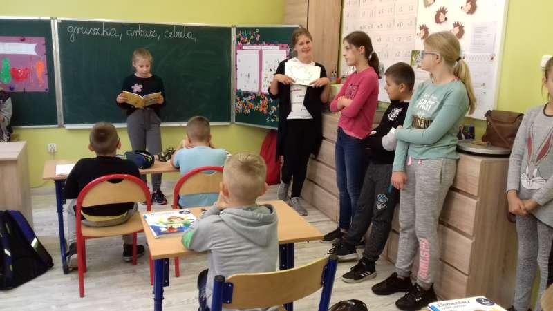 Dziewczynka stojąca przy stablicy na środku klasy czyta bajkę siedzącym w ławkach dzieciom.