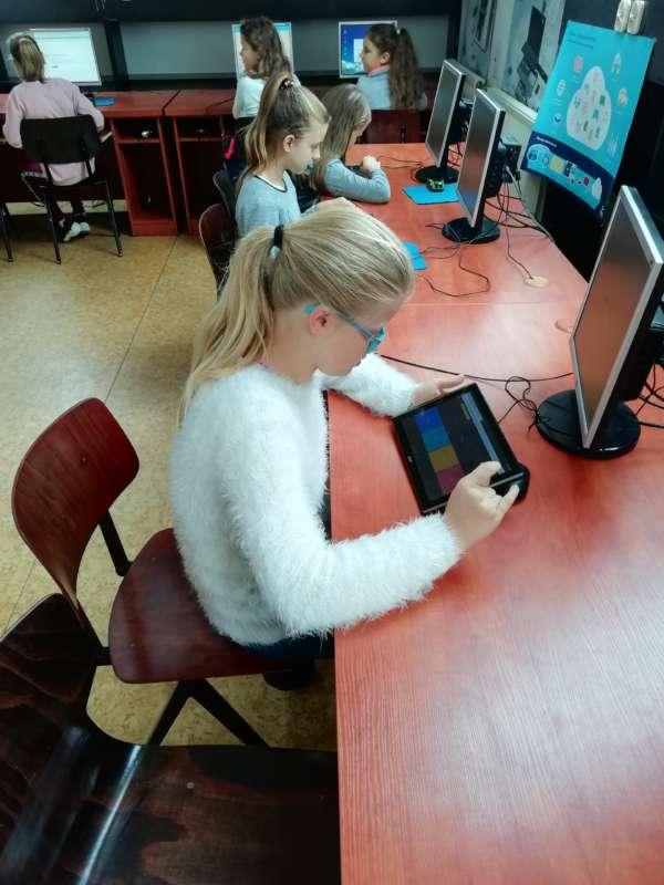 Dziewczynki siedzące przy stołach z monitorami komputerowymi wykonują obliczenia na tabletach.