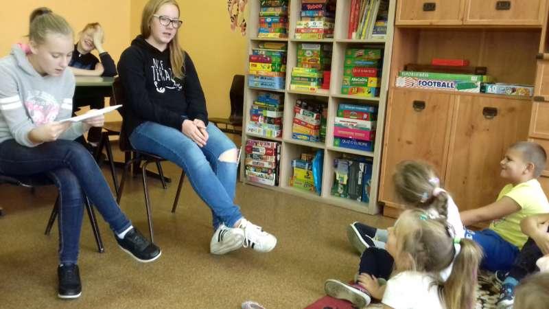 Dwie dziewczynki z klasy VII siedzą na krzesłach i czytają bajki zgdomadzonym przed nimi na dywanie dzieciom.