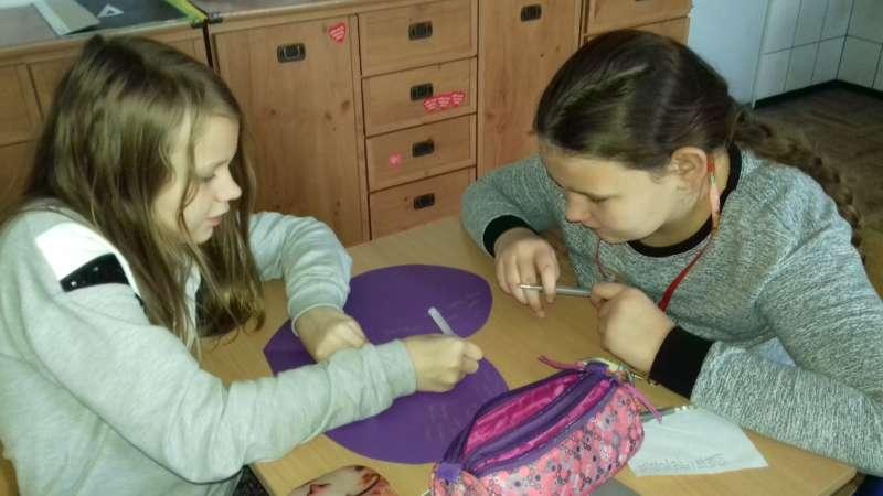 Dziewczynki siedzące w ławce szkolnej, wpisują długopisem nazwy książek na sercu wyciętym z papieru.