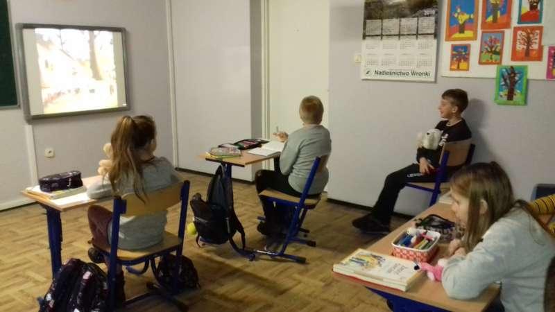 Dzieci siedzące w szkolnych ławkach oglądają bajkę na ekranie, zawieszonym w klasie obok tablicy.