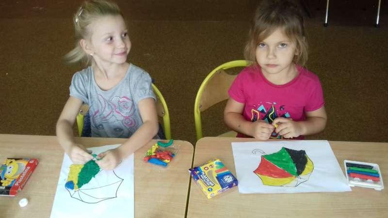 Dwie dziewczynki siedzące w szkolnych ławkach kolorują kredkami olejnymi obrazki przedstawiające parasole.