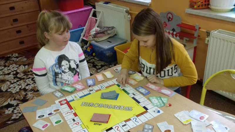 Dwie dziewczynki siedzące przy stoliku grają w grę planszową Eurobusiness