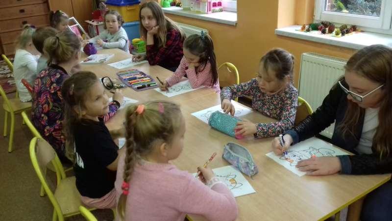 Małe dziewczynki, siedzące przy połączonych ławkach, kolorują rysunki z kotkami.