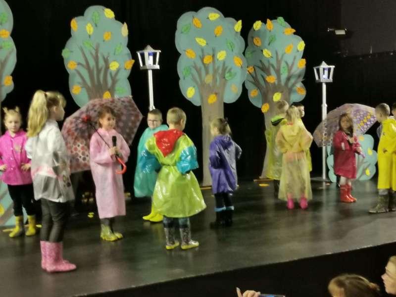 Dzieci ubrane w różnokolorowe przeciwdeszczowe poncho foliowe, śpiewają na scenie piosenkę.