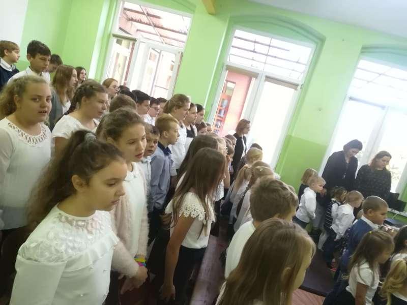 """Dzieci ubrane na galowo śpiewają """"Mazurka Dąbrowskiego""""."""
