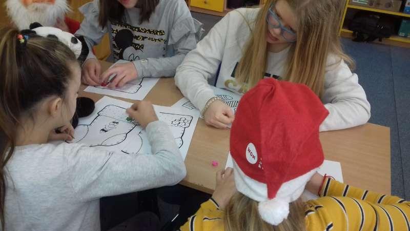 Dzieci siedzące przy stole kolorują kredkami obrazki skarpetek.