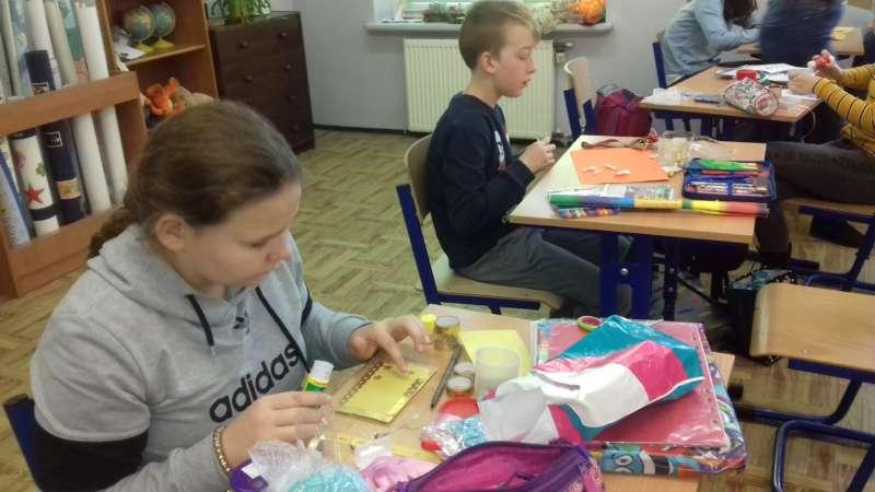 Dzieci siedzące w ławkach szkolnych, przygotowują własnoręcznie kartki bożonarodzeniowe.