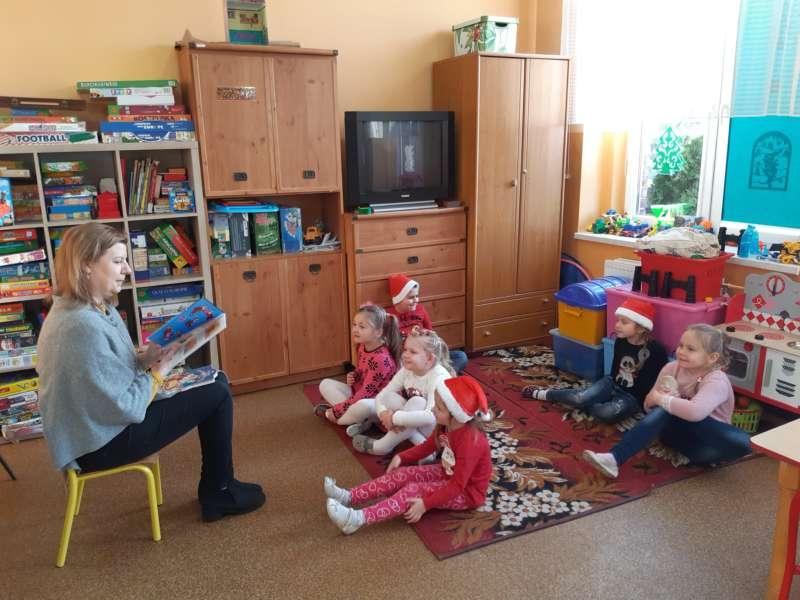 Pani Kasia z biblioteki wiejskiej siedząc na taborecie czyta bajkę dzieciom, siędzącym przed nią na dywanie.