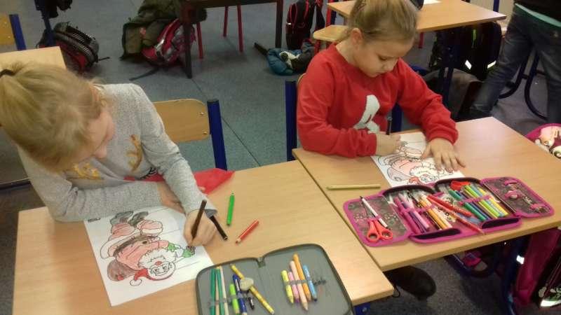 Dwie dziewczynki siedzące w ławkach kolorują kredkami obrazki z Św. Mikołajem.