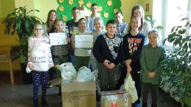 Dzieci stoją trzymając produkty żywnościowe oraz artykuły chemiczne.