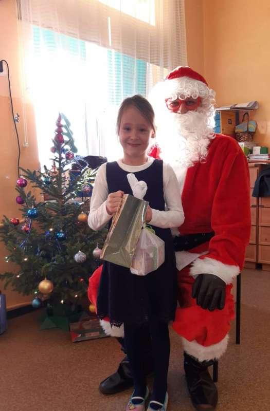 Dziewczynka trzymająca prezenty stoi obok Świetego Mikołaja oraz choinki.