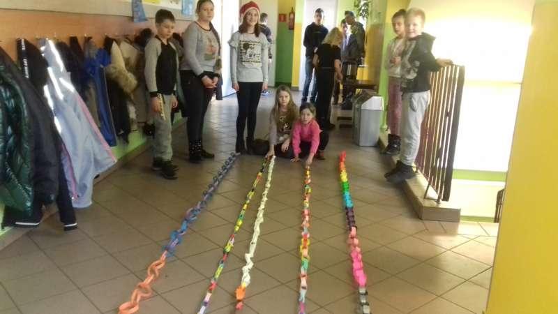 Dzieci układają łańcuch choinkowy wzdłuż korytarza szkolnego.