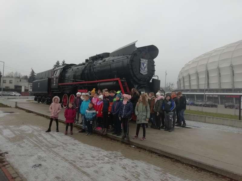 Dzieci w zimowych kurkach i czapkach pozują do zdjecia obok lokomotywy, znajdującej się przy stadionie Lecha Poznań na ul. Bułgarskiej.
