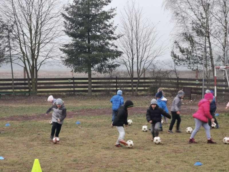 Dzieci ćwiczą z piłkami nożnymi na boisku szkolnym.
