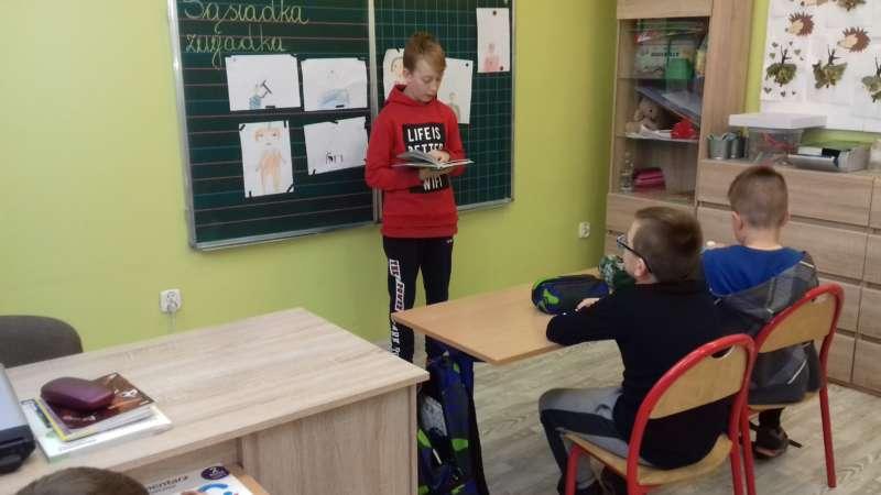 Chłopiec stojący przy tablicy czyta wierszyki przed całą klasą.