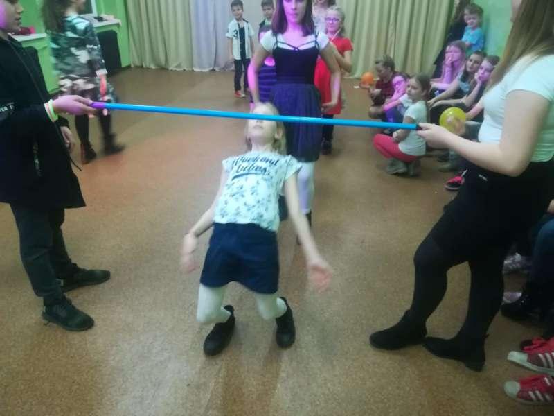 Dzieci kolejno przechodzą pod tyczką podczas zabawy w limbo.