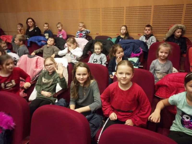 Gromadka dzieci zajmuje trzy rzędy foteli teatralnych podczas przedstawienia.