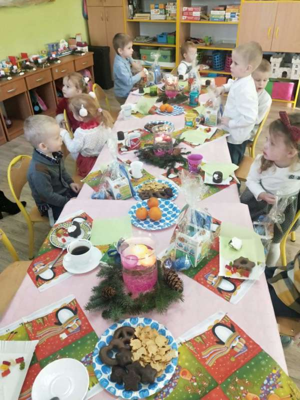 Dzieci siedzą przy kolorowym, suto zastawionym świątecznym stole.