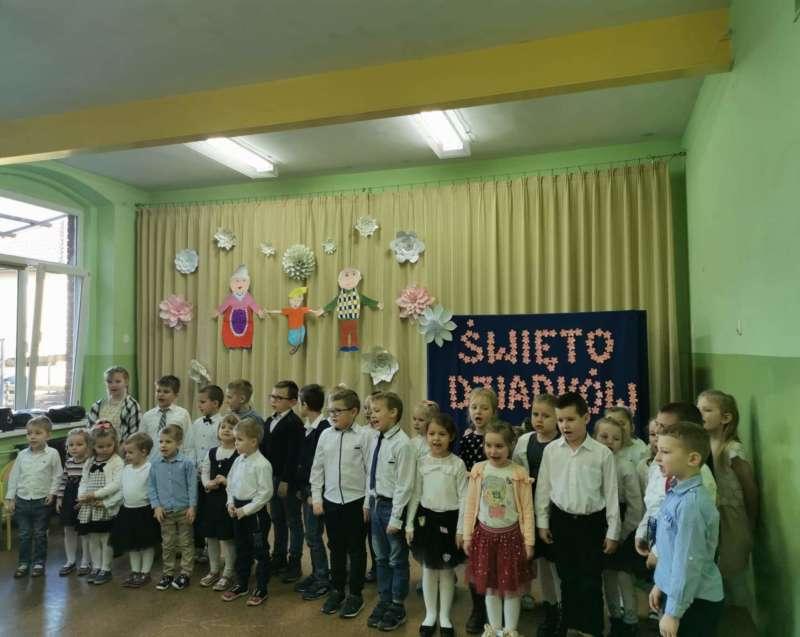 Gromadka dzieci śpiewa piosenkę przed zgdromadzoną na sali gimnastycznej widownią z okazji Święta Babci i Dziadka