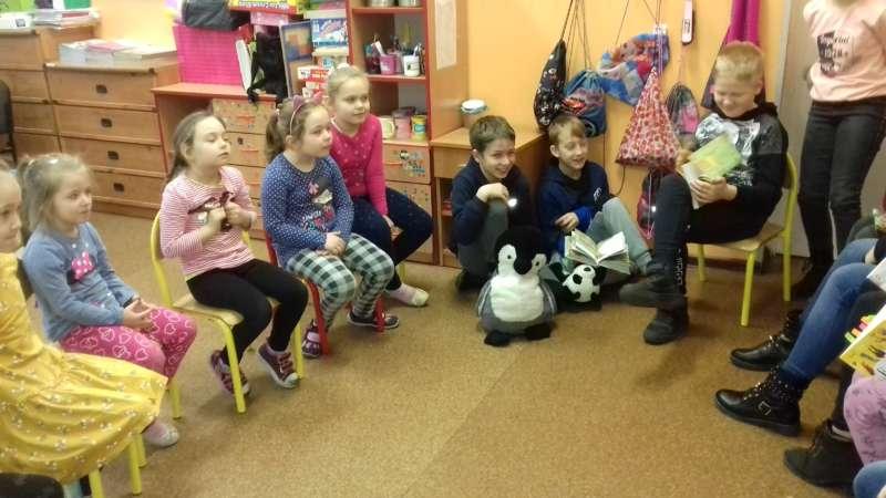 Uczniowie klas V czytają bajki zebranym wokół nich dzieciom.