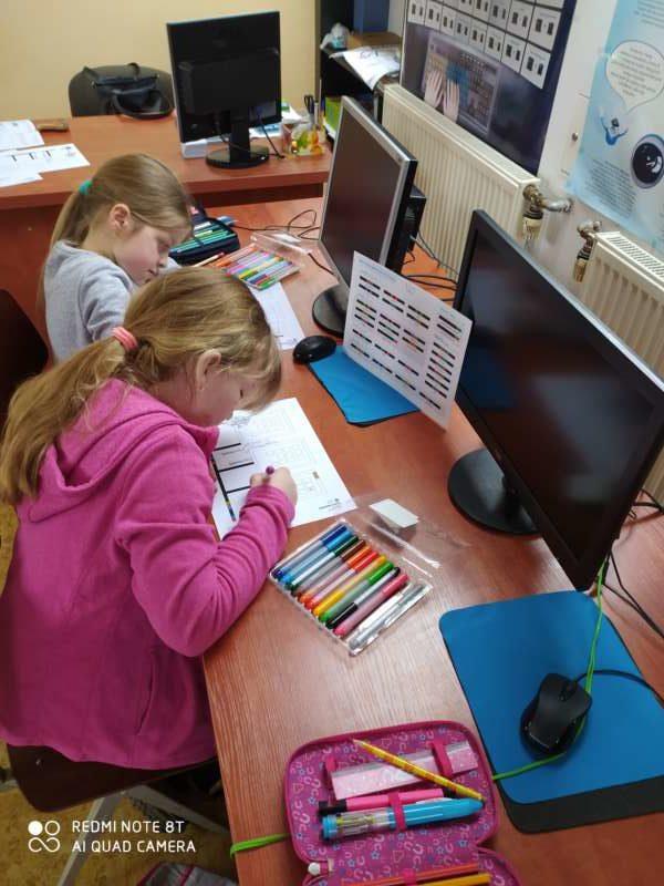 Dwie dziewczynki siedzą na krzesłach przed biurkiem z monitorami komputerów, kolorując kartki pisakami.